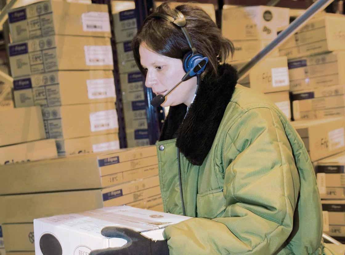 Un operario realiza tareas de preparación de pedidos con un sistema de voice picking